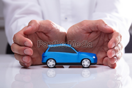 businessman protecting blue car