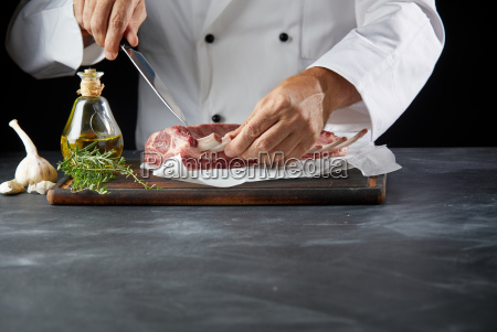chef cutting lamb chop with knife