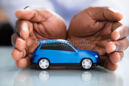 businessmans hand protecting blue toy car