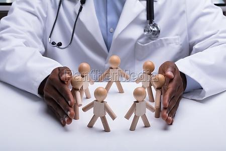 doctors hand protecting circular wooden figure