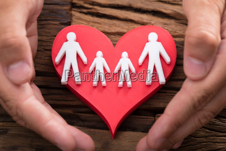 person protecting red heart with family