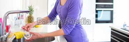 young woman washing dishes in the