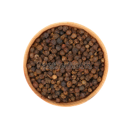 wooden bowl full of black peppercorns