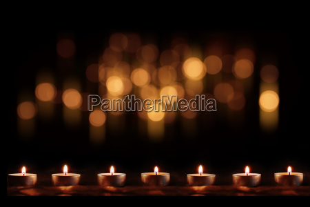 burning candles with festive golden bokeh