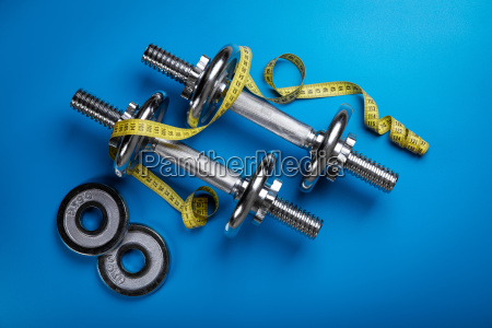 dumbells with yellow measuring tape on