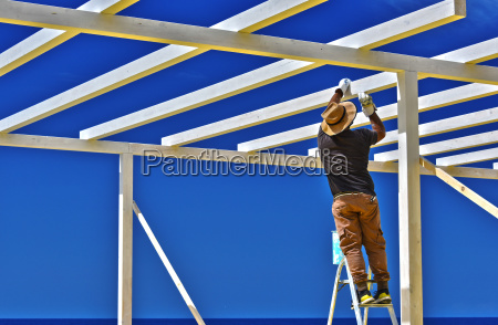 man putting a wooden structure on