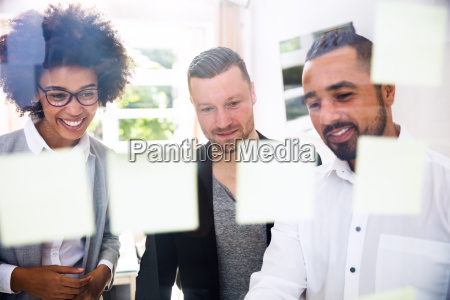 group of businesspeople sticking adhesive notes
