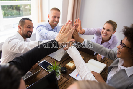 businesspeople giving high five in office