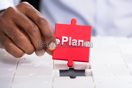 hand holding jigsaw puzzle with plan