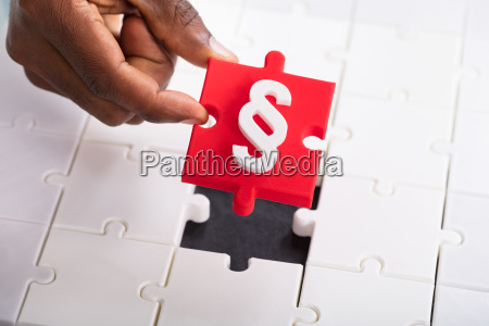 hand holding paragraph symbol jigsaw puzzle