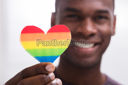 smiling man holding rainbow heart in
