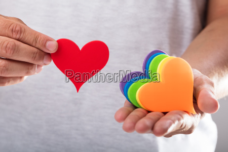 mans hand holding various hearts