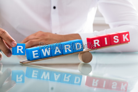 businessman showing unbalance between reward and