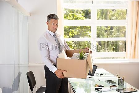 unhappy businessman carrying belongings in cardboard