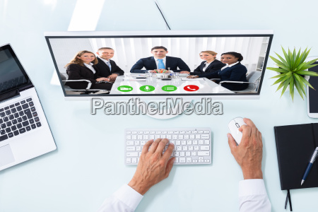 businessman videoconferencing with colleagues on computer