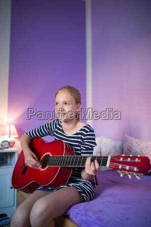 teenage girl playing a guitar