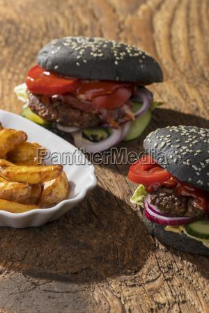 closeup of black hamburgers on wood