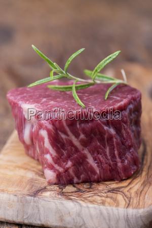 raw steak on dark wood