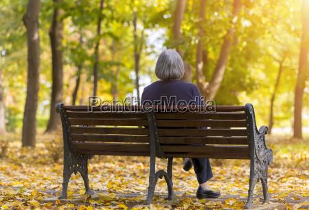 elderly woman sitting on a bench