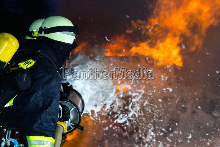 firefighter firemen extinguishing a large