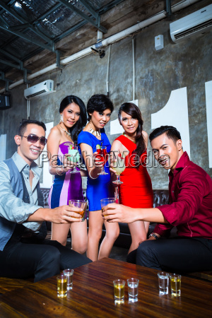 asian friends drinking cocktails in nightclub