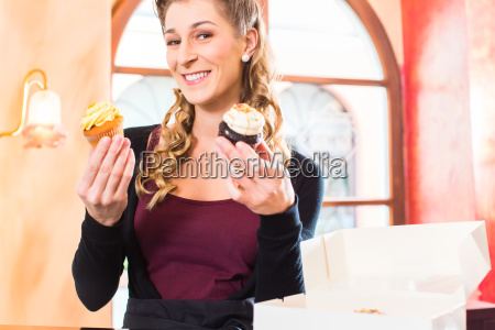woman presenting cupcakes of confectionery