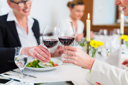women on business lunch toasting with