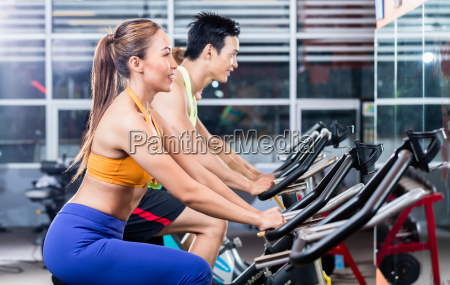sportive asian couple doing indoor cycling