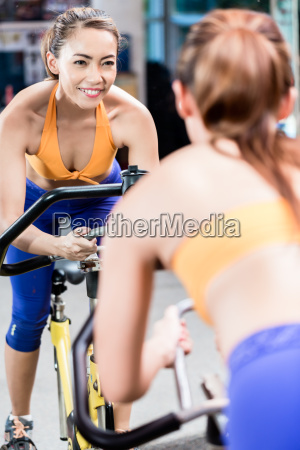 young sportive woman pedaling during indoor
