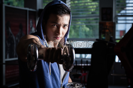 young man reaching out with dumbbell