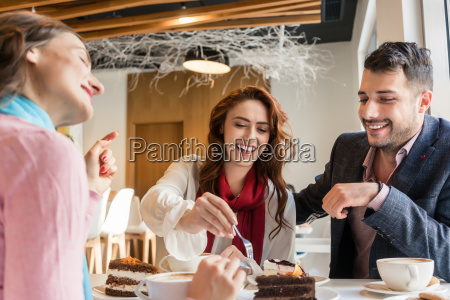 three friends smiling while eating delicious