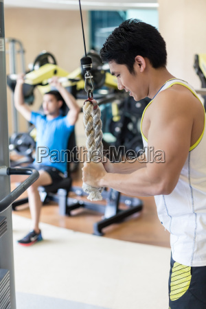 strong young man exercising triceps pushdown