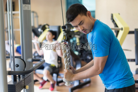 young man exercising triceps pushdown during