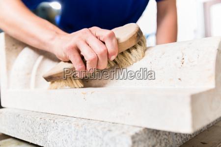 stonemason brushing stone dust off workpiece