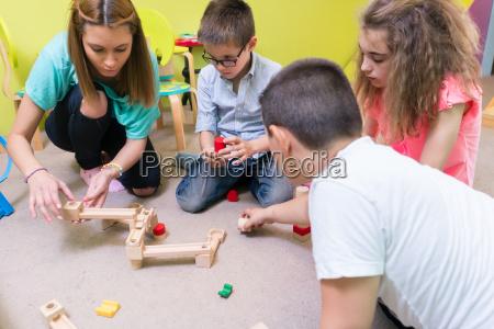 dedicated kindergarten teacher helping children with