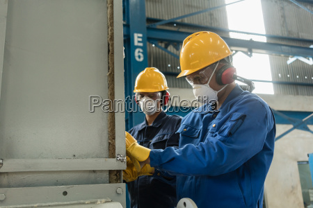 two blue collar workers wearing protective