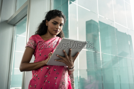 portrait of young indian woman using