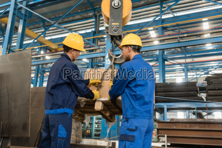 two workers handling heavy loading lifted