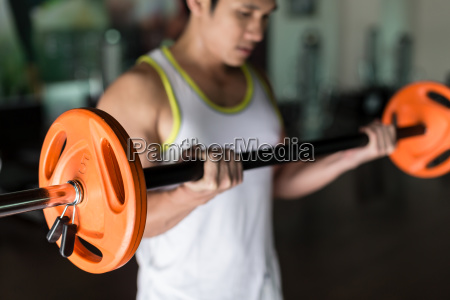 determined young man holding a barbell