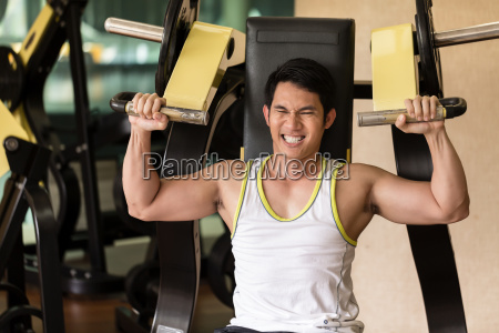 strong young man exercising for arms