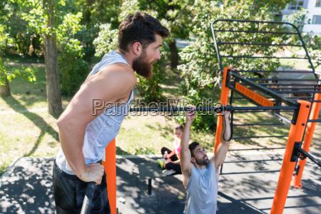 two muscular young men doing bodyweight