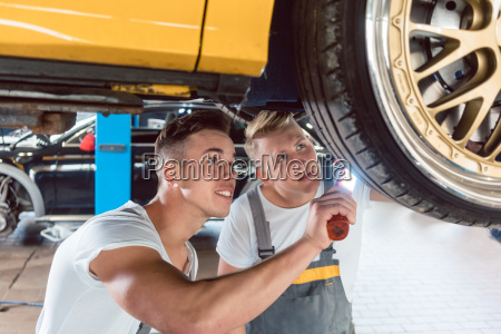 two dedicated auto mechanics tuning a