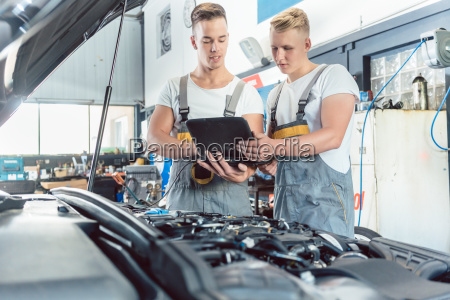 experienced auto mechanic using a laptop