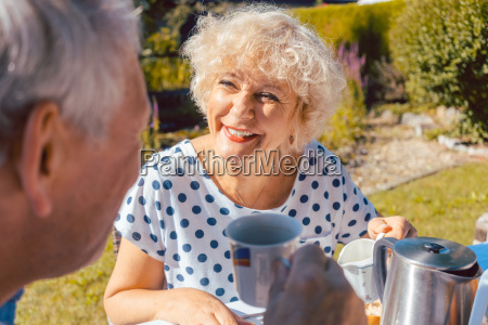 happy elderly couple eating breakfast in