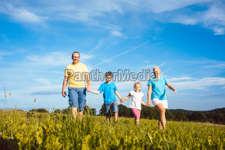 family holding hands running over meadow