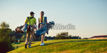 happy couple wearing golf outfits while