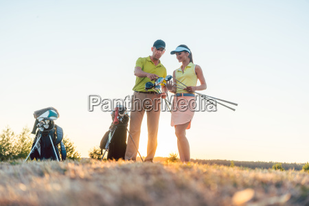 golf instructor teaching a young woman