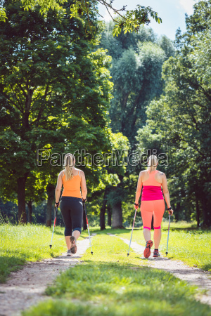 mother and daughter doing nordic walking