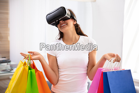 happy young woman wearing virtual reality