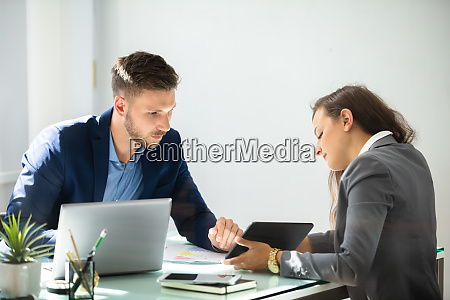 two businesspeople using digital tablet